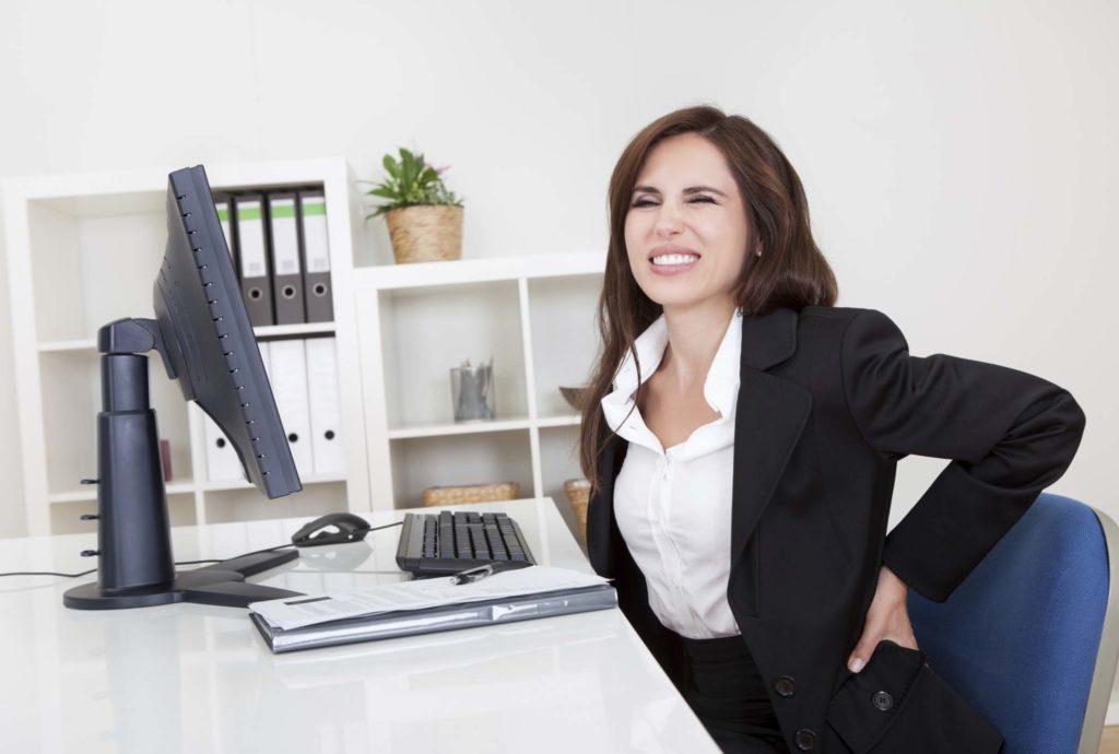 soulager le mal de dos par le sport jeune femme qui a mal au dos au bureau